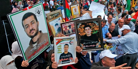 Palestinians hold portraits of relatives jailed in Israeli prisons as they protest to demand for their release during a demonstration to mark the Prisoners' Day in the northern West Bank city of Nablus on April 17, 2018. / AFP PHOTO / JAAFAR ASHTIYEH        (Photo credit should read JAAFAR ASHTIYEH/AFP/Getty Images)