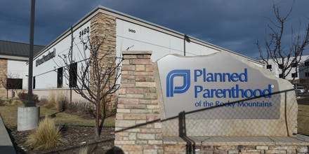 A shadow from a chain link fence falls across the Planned Parenthood of the Rocky Mountains sign on Monday, Feb. 15, 2016, in Colorado Springs, Colo. The Colorado Springs' Planned Parenthood clinic reopened Monday, nearly three months after a gunman killed three people and injured nine others. The clinic will offer all of its services - including contraceptives, cancer screenings and abortions - but during fewer appointments, and in only part of the building while construction crews continue repairs elsewhere. (Jerilee Bennett/The Gazette via AP) MAGS OUT; MANDATORY CREDIT