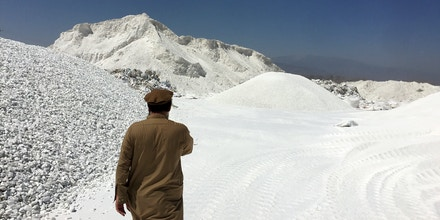 A man walks among piles of talc at a processing plant near Jalalabad in 2017.