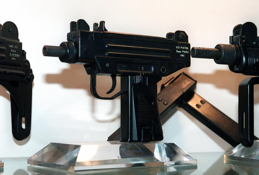 RAMAT HASHARON, ISRAEL:  An Uzi pistol (C) is displayed next to the larger Uzi submachine gun models, at the Israeli Military Industries (IMI) in Ramat Hasharon 11 November. The IMI, maker of the famed Israeli guns vowed to fight efforts by US gun control advocates to bar imports of what they consider a weapon of choice for violent criminals. The Uzi sale is expected to reap 7 million dollars in two to three years in the US hand weapons market. (Photo credit should read SVEN NACKSTRAND/AFP/Getty Images)