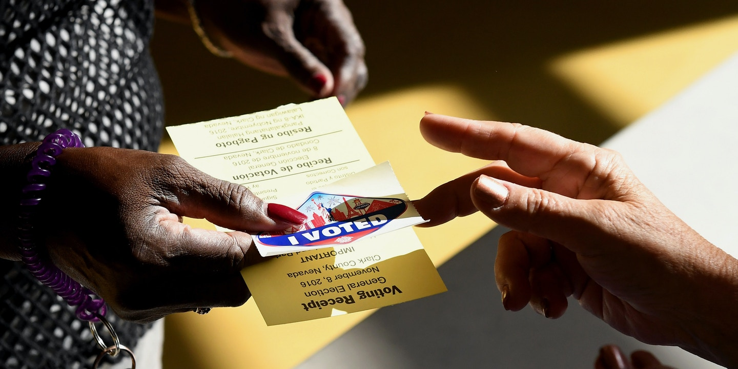 "NORTH LAS VEGAS, NV - NOVEMBER 08:  A poll worker gives a voter a Las Vegas Strip-themed ""I Voted"" sticker after taking back her voter activation card at a polling station at Cheyenne High School on Election Day on November 8, 2016 in North Las Vegas, Nevada. Americans across the nation are picking their choice for the next president of the United States.  (Photo by Ethan Miller/Getty Images)"