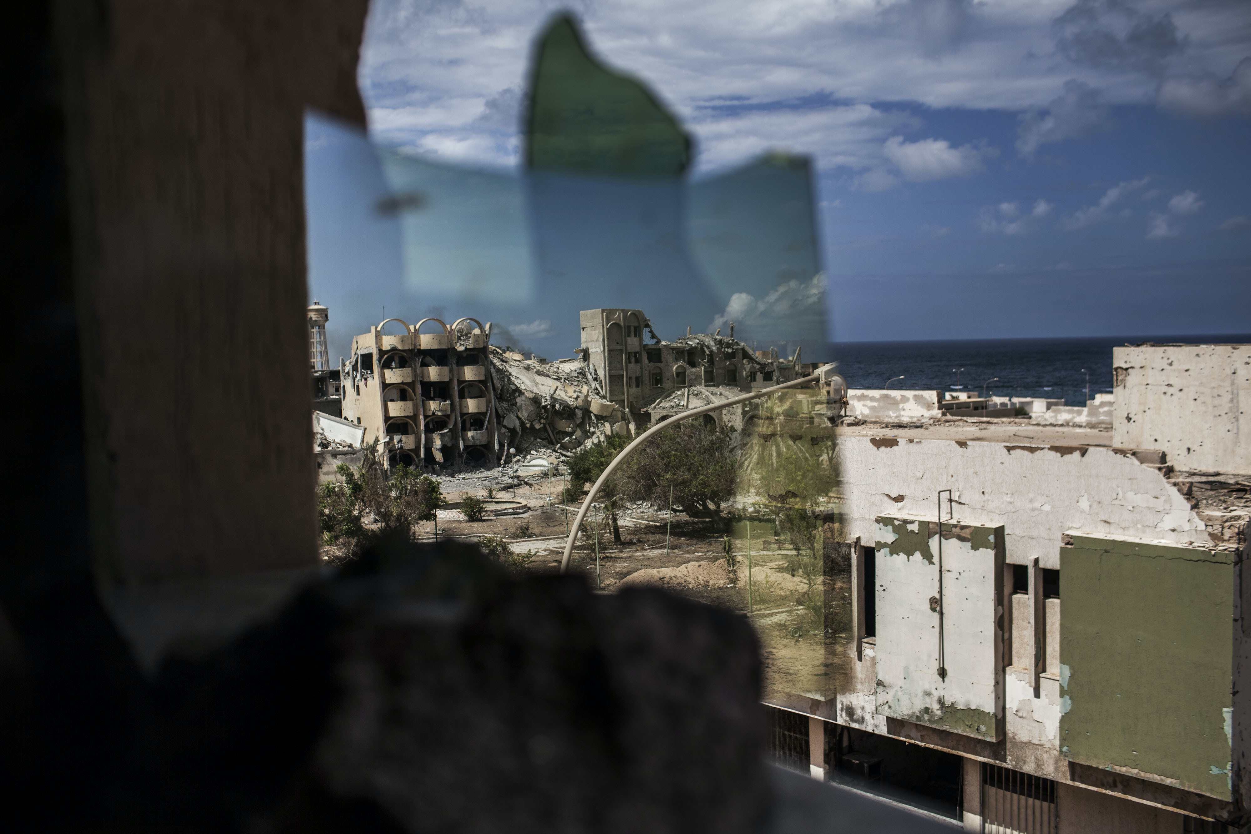 The view from a hidden position looking into a mirror, where fighters of the Libyan forces affiliated to the Tripoli government remain out of sight from snipers and scan for possible targets in the street outside, from their vantage point inside a building at the western front line in Sirte, Libya, Tuesday, Sept. 27, 2016. (AP Photo/Manu Brabo)