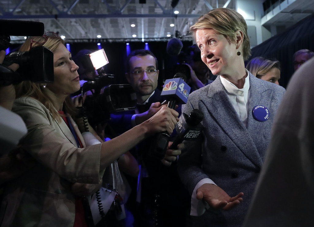 New York gubernatorial nominee Cynthia Nixon, right, answers questions for the media as she leaves the New York state Democratic convention, Wednesday, May 23, 2018, in Hempstead, N.Y. (AP Photo/Julie Jacobson)