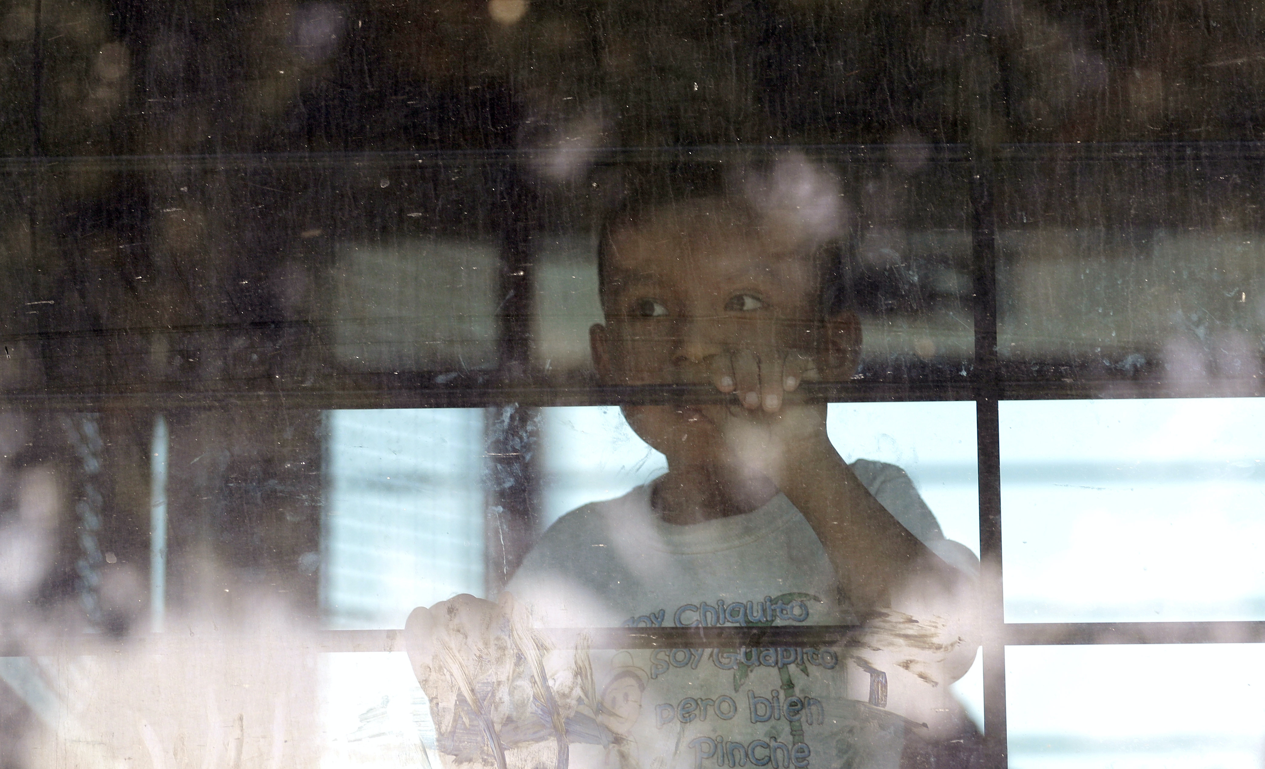 An immigrant child looks out from a U.S. Border Patrol bus as protesters block the street outside the U.S. Border Patrol Central Processing Center Saturday, June 23, 2018, in McAllen, Texas. Additional law enforcement officials were called in to help control the crowd and allow the bus to move. (AP Photo/David J. Phillip)