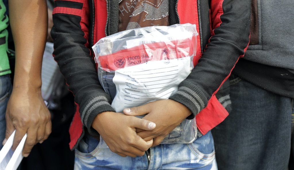 FILE - In this Friday, June 22, 2018, file photo, a young immigrant holds his belongings in a Homeland Security bag while waiting to enter the bus station after being processed and released by U.S. Customs and Border Protection, in McAllen, Texas. Foster care advocates say the government won't likely be able to reunite thousands of children separated from parents who crossed the border illegally, and some will end up in an American foster care system that is stacked against Latinos and other minorities. (AP Photo/David J. Phillip, File)