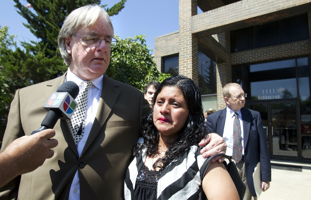 Attorney Curtis Woods, left, clutches his client, Encarnacion Bail Romero, minutes after a Greene County judge in Springfield, Mo., terminated her parental rights to the son she last held five years ago when he was seven months old. Romero lost custody of her 6-month-old son, Carlos, after she was arrested during an ICE raid on a chicken plant in Missouri. While she was imprisoned, her baby was first cared for by relatives and later adopted, against her wishes, by a Missouri couple after a judge said the child was better off with them. (AP Photo/The Kansas City Star, Tammy Ljungblad) ALL KANSAS CITY TELEVISION OUT, ONLINE OUT