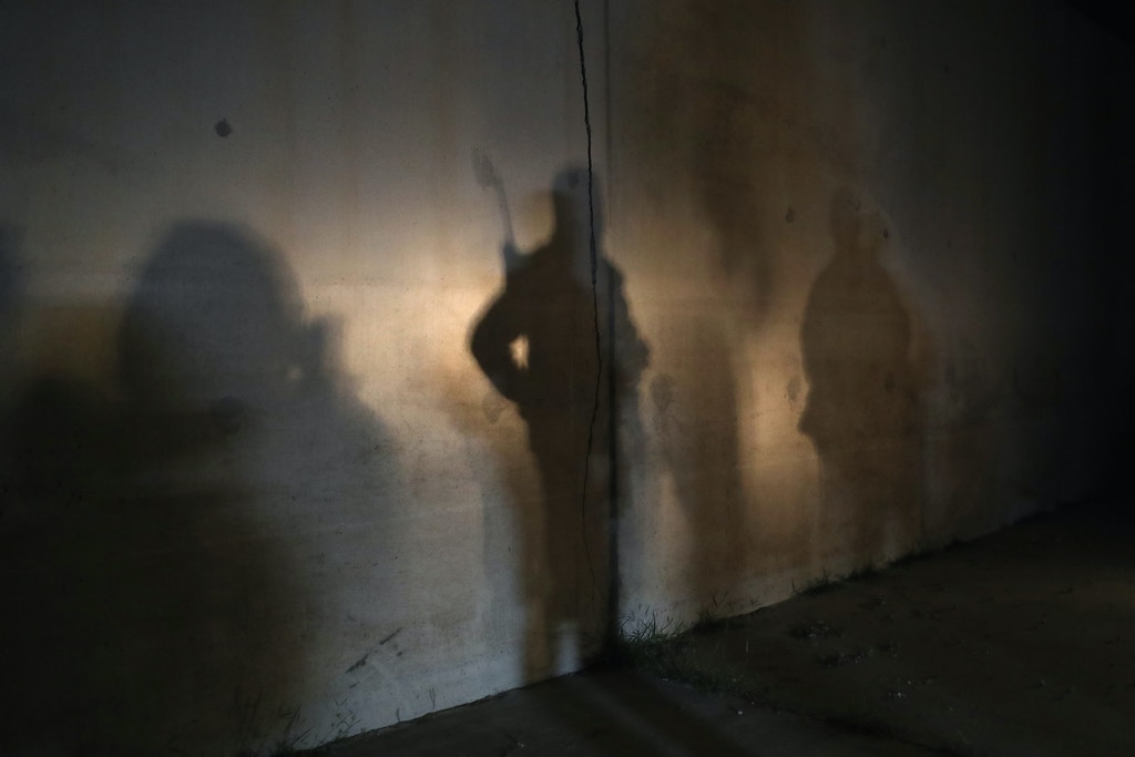 MCALLEN, TX - FEBRUARY 22:  Shadows from U.S. Border Patrol agents stand near captured undocumented immigrants on February 22, 2018 near McAllen, Texas. Seen by cameras in a Border Patrol survellance tower, the group had crossed from Mexico into Texas only moments before.  (Photo by John Moore/Getty Images)