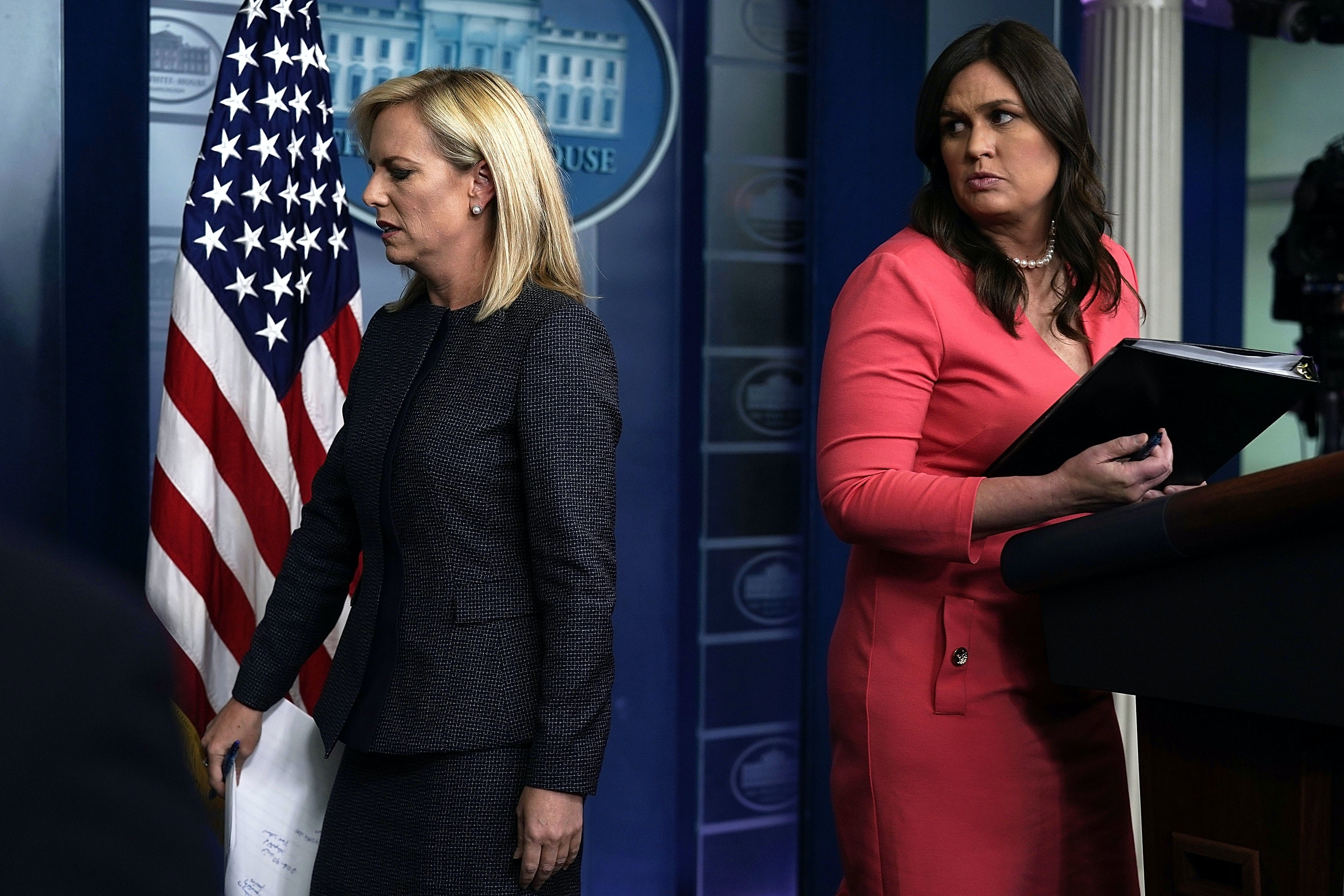 WASHINGTON, DC - JUNE 18:  U.S. Secretary of Homeland Security Kirstjen Nielsen (L) leaves after she briefed members of the press as White House Press Secretary Sarah Sanders (R) looks on during a White House daily news briefing at the James Brady Press Briefing Room of the White House June 18, 2018 in Washington, DC. Nielsen joined White House Press Secretary Sarah Sanders at the daily news briefing to answer questions from members of the White House Press Corps.   (Photo by Alex Wong/Getty Images)