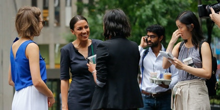 Alexandria Ocasio-Cortez, second from left, the winner of the Democratic primary in New York's 14th Congressional District, speaks with supporters, Wednesday, June 27, 2018, in New York.  The 28-year-old political newcomer upset U.S. Rep. Joe Crowley, says she brings an