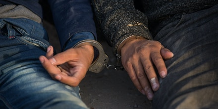 TOPSHOT - After being apprehended by Border Patrol, illegal immigrants wait to be transported to a central processing center shortly after they crossed the border from Mexico into the United States on Monday, March 26, 2018 in the Rio Grande Valley Sector near McAllen, Texas. - An estimated 11 million undocumented immigrants live in the United States, many of them Mexicans or from other Latin American countries. (Photo by Loren ELLIOTT / AFP)        (Photo credit should read LOREN ELLIOTT/AFP/Getty Images)