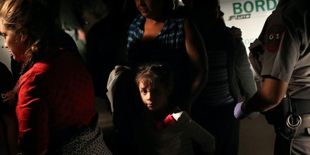 MCALLEN, TX - JUNE 12:  U.S. Border Patrol agents detain a group of Central American asylum seekers near the U.S.-Mexico border on June 12, 2018 in McAllen, Texas. The group of women and children had rafted across the Rio Grande from Mexico and were detained before being sent to a processing center for possible separation. Customs and Border Protection (CBP) is executing the Trump administration's