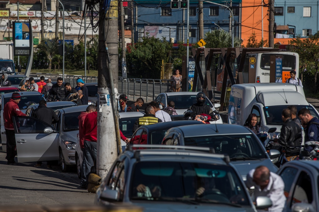 SAO PAULO, BRAZIL - MAY 29: Drivers await the arrival of fuel to supply motorcycles and cars during the trucker's strike on May 29, 2018 in San Paulo, Brazil. The queues to fuel the vehicles are reaching kilometers in the few gas stations that have fuel. Only 5% of the city's gas stations are operating due to the truckers strike. The strike is on it's eighth day and reaches almost every state in the country. Financial losses already exceed 10 billion dollars. (Photo by Victor Moriyama/Getty Images)