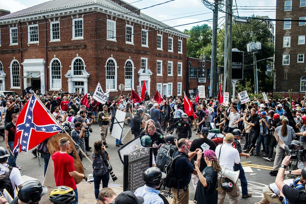CHARLOTTESVILLE, VIRGINIA - AUGUST 12: Protestors and white nationalists fight each other outside of Emancipation park at the Unite the Right Rally on August 12, 2017 in Charlottesville, Virginia. (Photo by Jason Andrew/Getty Images)