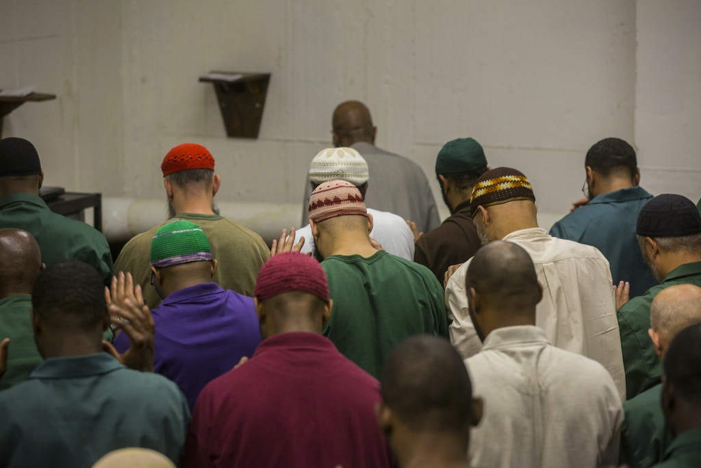 Muslim inmates during prayers on the last day of Ramadan at Sing Sing Correctional Facility in Ossining, N.Y., July 5, 2016. During Ramadan, Muslim inmates are entitled by federal law to observe their religious obligations, including eating meals only between sundown and sunrise, and Sing Sing, in particular, is known as the ultimate location for organize programs pertaining to Islam. (Hiroko Masuike/The New York Times)