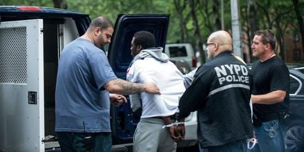 Members of the NYPD Gang Division raid the Manhattanville Houses and the Grant Houses early Wednesday morning holding warrants for more than 100 gang members wanted in connection for murder, and other gang related offenses, in New York, June 4, 2014. (Robert Stolarik/The New York Times)