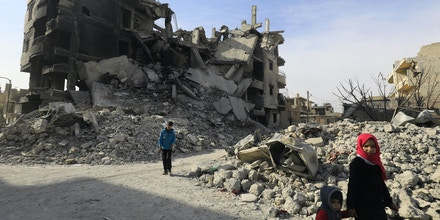Syrians walk amidst the debris of destroyed buildings in the northern Syrian city of Raqa, on January 11, 2018 after a huge military operation led on the ground by Kurdish fighters and in the air by US warplanes defeated jihadists from the Islamic State group but also left the city completely disfigured.Once home to around 300,000 people, Raqa's neighbourhoods were empty when it was declared retaken in mid-October. Three months on, despite the lack of infrastructure and the lingering threat of unexploded mines and bombs, a trickle of residents -- a few hundred families -- are attempting to return. / AFP PHOTO / DELIL SOULEIMAN (Photo credit should read DELIL SOULEIMAN/AFP/Getty Images)