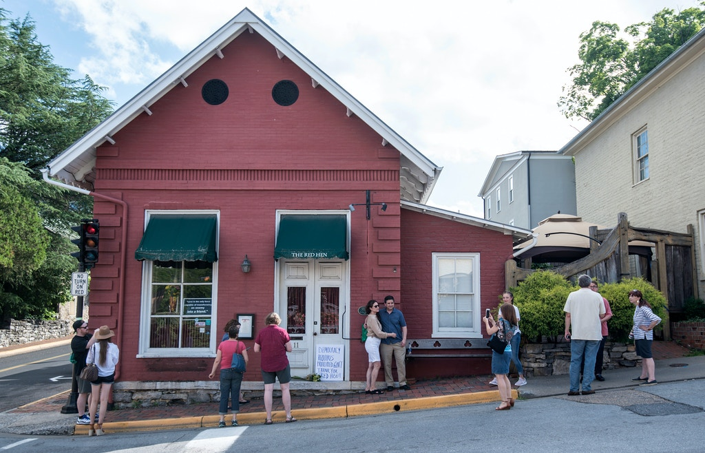 "Passersby gather to take photos in front of the Red Hen Restaurant, Saturday, June 23, 2018, in Lexington, Va. White House press secretary Sarah Huckabee Sanders said Saturday in a tweet that she was booted from the Virginia restaurant because she works for President Donald Trump. Sanders said she was told by the owner of The Red Hen that she had to ""leave because I work for @POTUS and I politely left."" (AP Photo/Daniel Lin)"