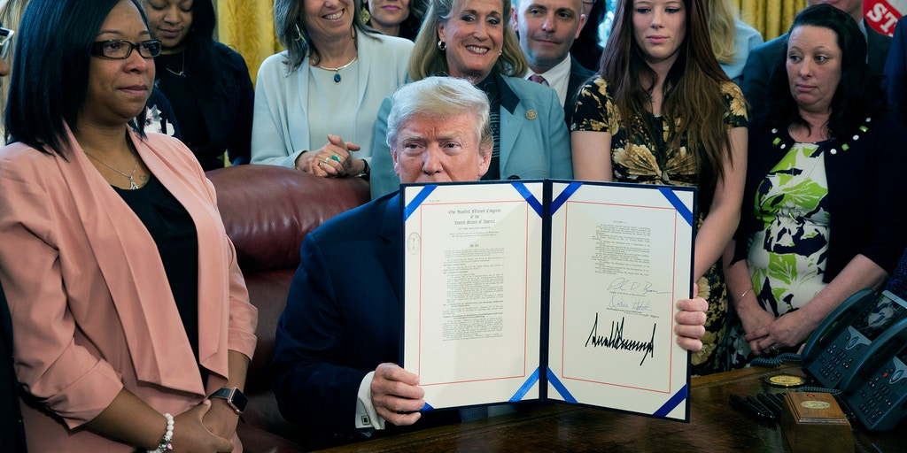 "WASHINGTON, DC - APRIL 11:  United States President Donald. J. Trump displays H.R. 1865, the ""Allow States and Victims to Fight Online Sex Trafficking Act of 2017"" after signing it into law at The White House on April 11, 2018 in Washington, DC. With Trump are victims and family members of victims of online sex trafficking and members of Congress who helped pass the bill. (Photo by Chris Kleponis-Pool/Getty Images)"
