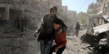 TOPSHOT - A Syrian man helps evacuate an injured victim following Syrian government air strikes on the Eastern Ghouta rebel-held enclave of Douma, on the outskirts of the capital Damascus on March 20, 2018.Syrian regime and allied forces battled to suppress the last pockets of resistance in and around Damascus while the beleaguered Kurds in the north braced for further Turkish advances. Assad has in recent months brought swathes of territory back under his control thanks to heavy Russian involvement, as well as support from other forces such as the Iran-backed Lebanese Hezbollah militia. Eastern Ghouta's main town of Douma remains under rebel control but even as a trickle of emergency medical evacuations was scheduled to continue, the regime continued to pound the enclave. / AFP PHOTO / HAMZA AL-AJWEH (Photo credit should read HAMZA AL-AJWEH/AFP/Getty Images)