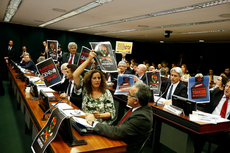 omissão especial da Câmara que analisa uma nova regulamentação para uso e produção de agrotóxicos votou e aprovou hoje o relatório do deputado Luiz Nishimori (PR-PR). Deputados em oposição ao texto levaram cartazes chamando o projeto de lei de PL do Veneno. A comissão acontece em Brasília, nesta segunda-feira.