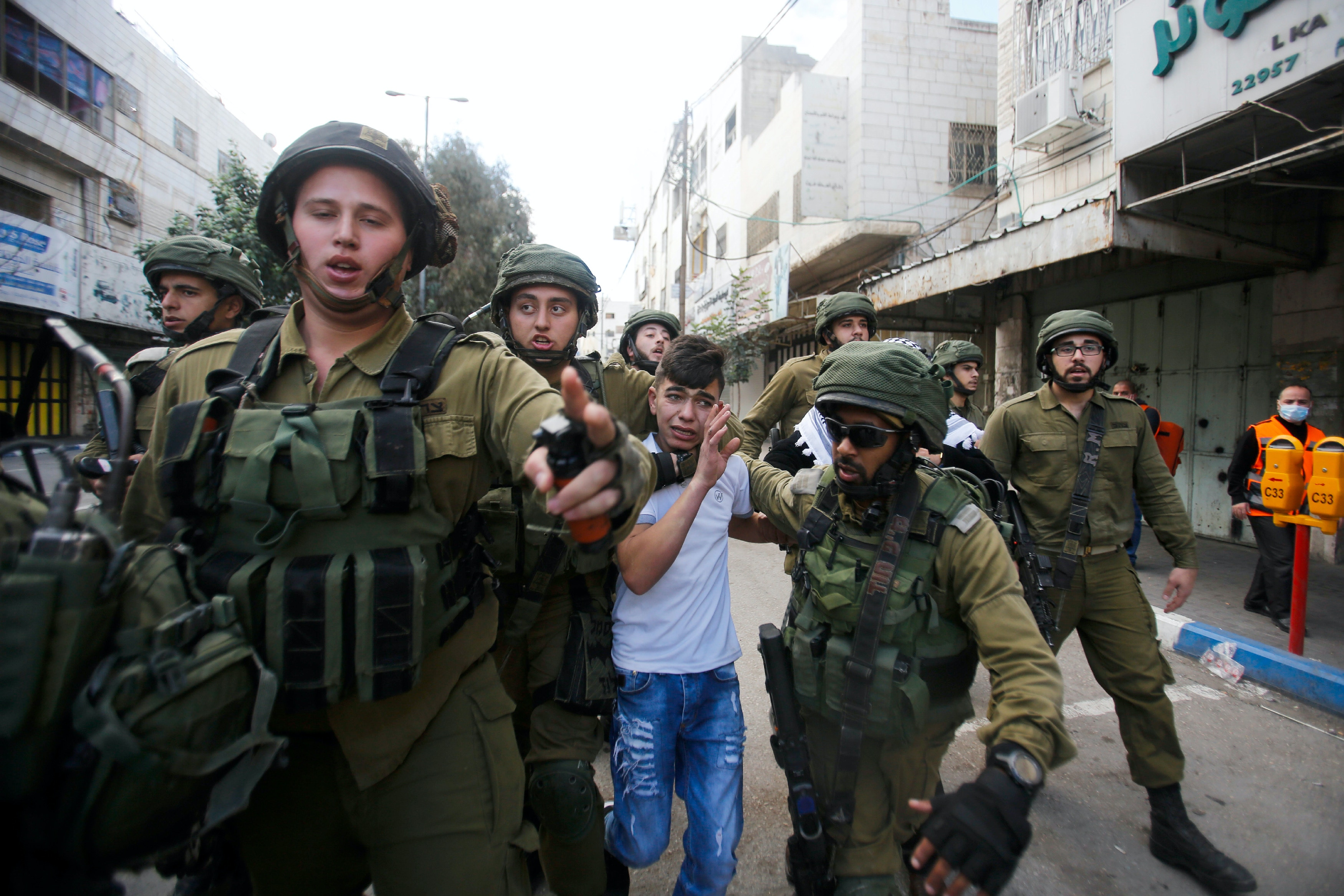 Israeli soldiers detain a Palestinian boy during clashes at a protest against U.S. President Donald Trump's decision to recognize Jerusalem as the capital of Israel in the West Bank city of Hebron, Friday, Dec. 15, 2017. (AP Photo/Nasser Shiyoukhi)