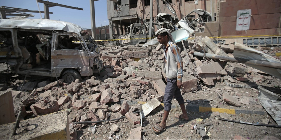 A man inspects rubble after a Saudi-led coalition airstrike in Sanaa, Yemen, Sunday, Feb. 4, 2018. Yemeni rebels say an air raid by the coalition fighting them struck a police building in the rebel-controlled capital, Sanaa, killing at least eight people. In a statement by their military media unit, the rebels, known as Houthis, say that a child was killed in the Sunday attack that badly damaged a department of records building and wounding over 50 people. (AP Photo/Hani Mohammed)