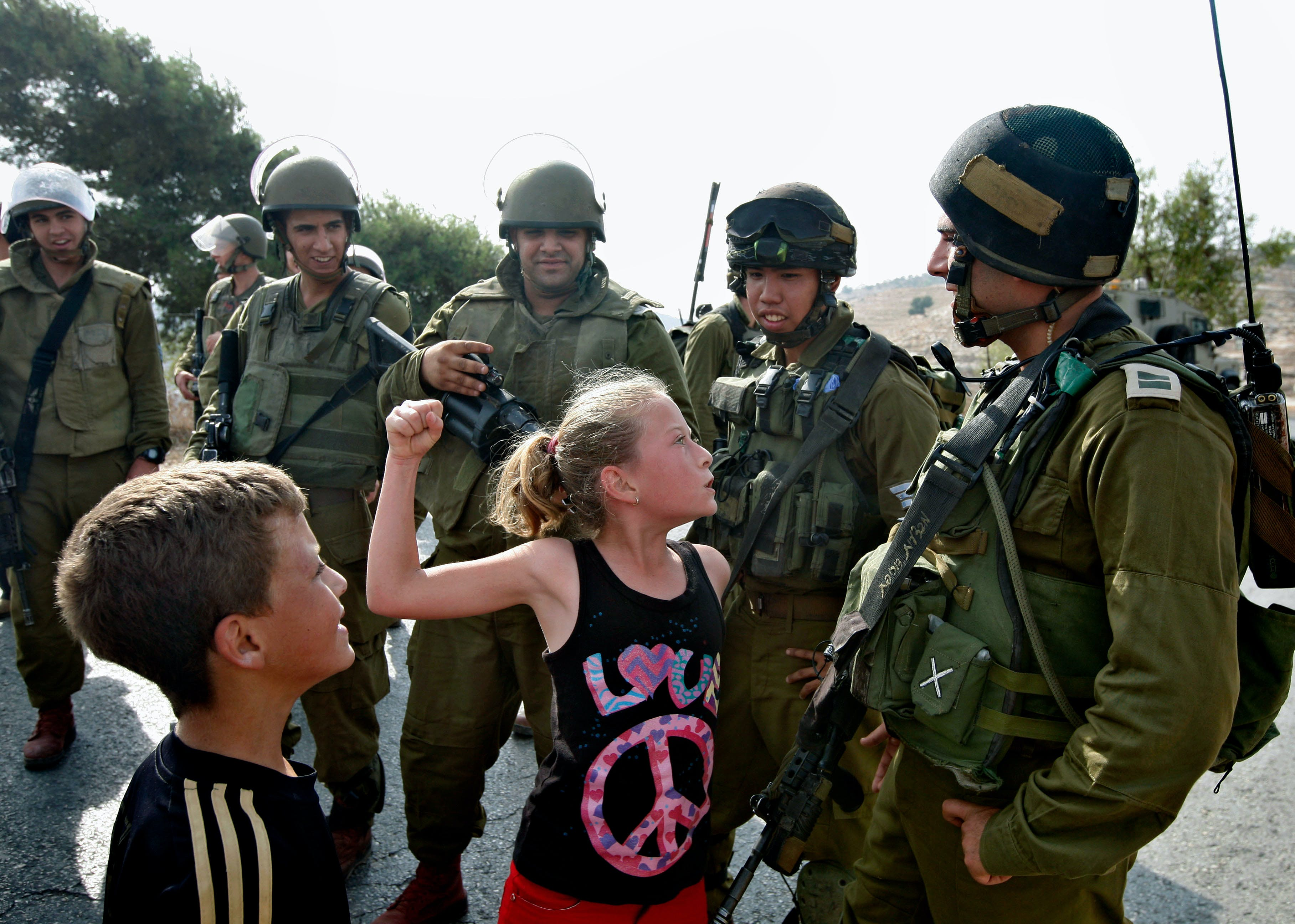 In this Nov. 2, 2012 photo, then 12-year-old Ahed Tamimi tries to punch an Israeli soldier during a protest, in the West Bank village of Nabi Saleh. Tamimi is to go on trial Tuesday, Feb. 13, 2018, before an Israeli military court, for slapping and punching two Israeli soldiers in December. Palestinians say her actions embody their David vs. Goliath struggle against a brutal military occupation, while Israel portrays them as a staged provocation meant to embarrass its military. Tamimi is one of an estimated 350 Palestinian minors in Israeli jails. (AP Photo/Majdi Mohammed)