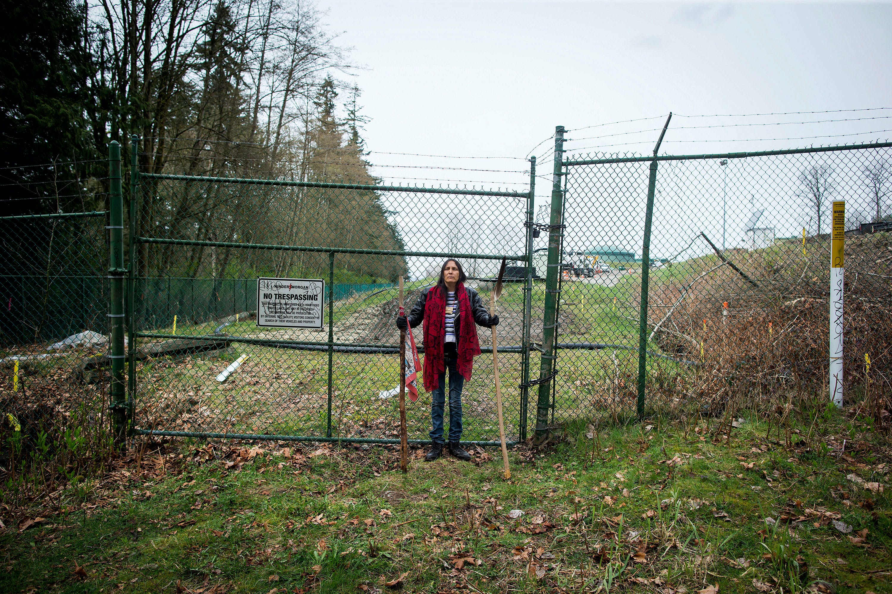 Kat Roivas, who is opposed to the expansion of the Kinder Morgan Trans Mountain pipeline, stands at an access gate at the company's property near an area where work is taking place, in Burnaby, B.C., on Monday April 9, 2018. The Houston, Texas, based company announced Sunday it has suspended all non-essential activities and related spending on the pipeline expansion that would carry Alberta bitumen to an export terminal near Vancouver. (Darryl Dyck/The Canadian Press via AP)
