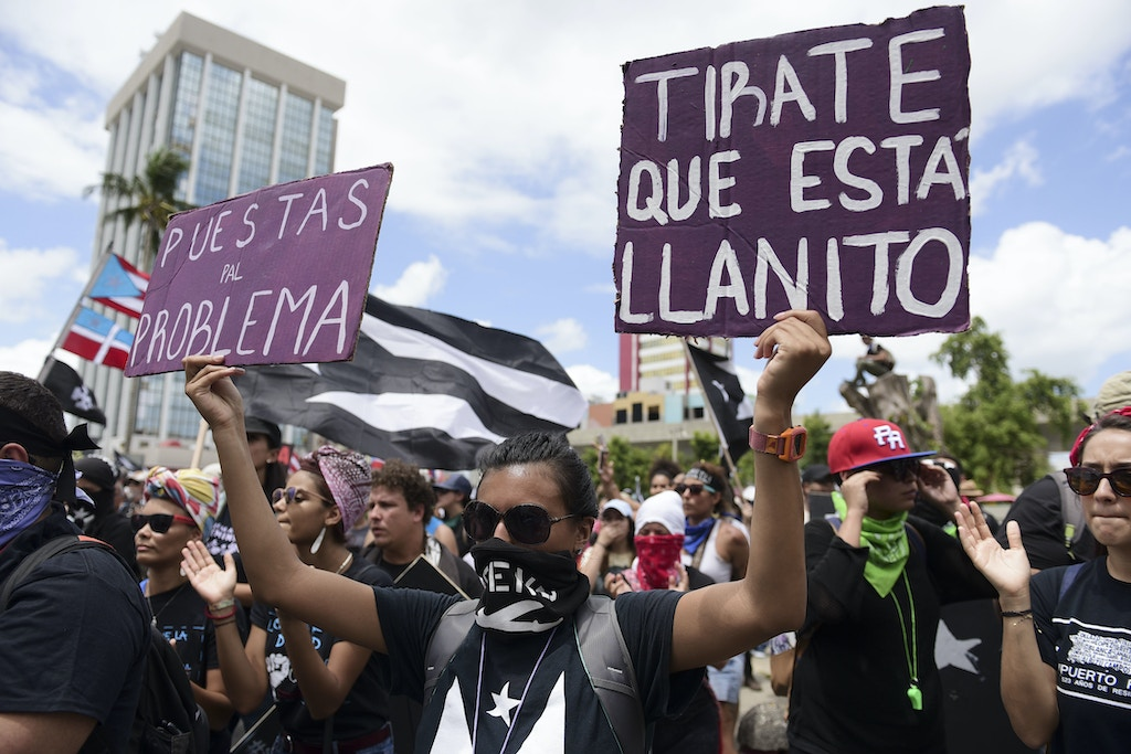 Thousands of Puerto Ricans march to protest pension cuts, school closures and slow hurricane recovery efforts as anger grows across the U.S. territory over looming austerity measures, in San Juan, Puerto Rico, Tuesday, May 1, 2018. (AP Photo/Carlos Giusti)