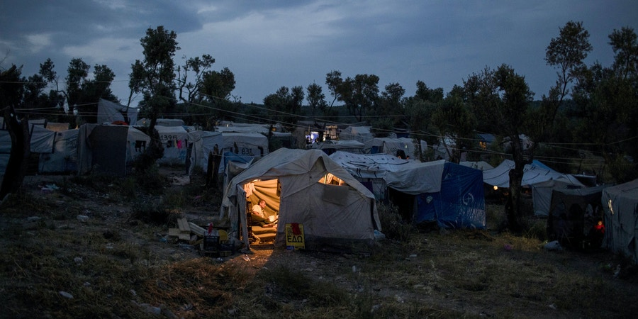 "In this Saturday, May 5, 2018 photo a Syrian man reads inside his tent at a makeshift camp outside Moria on the northeastern Aegean island of Lesbos, Greece. Currently, asylum seekers on five Aegean Sea islands _ Lesbos, Chios, Samos, Leros, and Kos _ are banned from traveling onto the Greek mainland as part of the European Union's controversial ""containment policy."" (AP Photo/Petros Giannakouris)"
