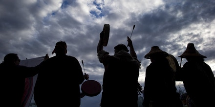 An Indigenous man raises his drum above his head as he and others are silhouetted while singing during a protest against the Kinder Morgan Trans Mountain Pipeline expansion in Vancouver on Tuesday May 29, 2018. The federal Liberal government is spending $4.5 billion to buy Trans Mountain and all of Kinder Morgan Canada's core assets, Finance Minister Bill Morneau said Tuesday as he unveiled the government's long-awaited, big-budget strategy to save the plan to expand the oil sands pipeline. (Darryl Dyck/The Canadian Press via AP)