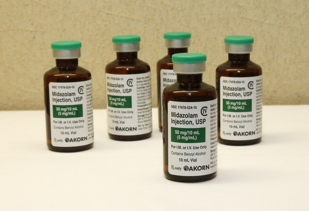FILE - This July 25, 2014 file photo shows bottles of the sedative midazolam at a hospital pharmacy in Oklahoma City. Supreme Court justices engaged in an impassioned debate on April 29, 2015, about capital punishment, trading unusually combative words in a case involving a drug used in several botched executions. (AP Photo/Sue Ogrocki, File)