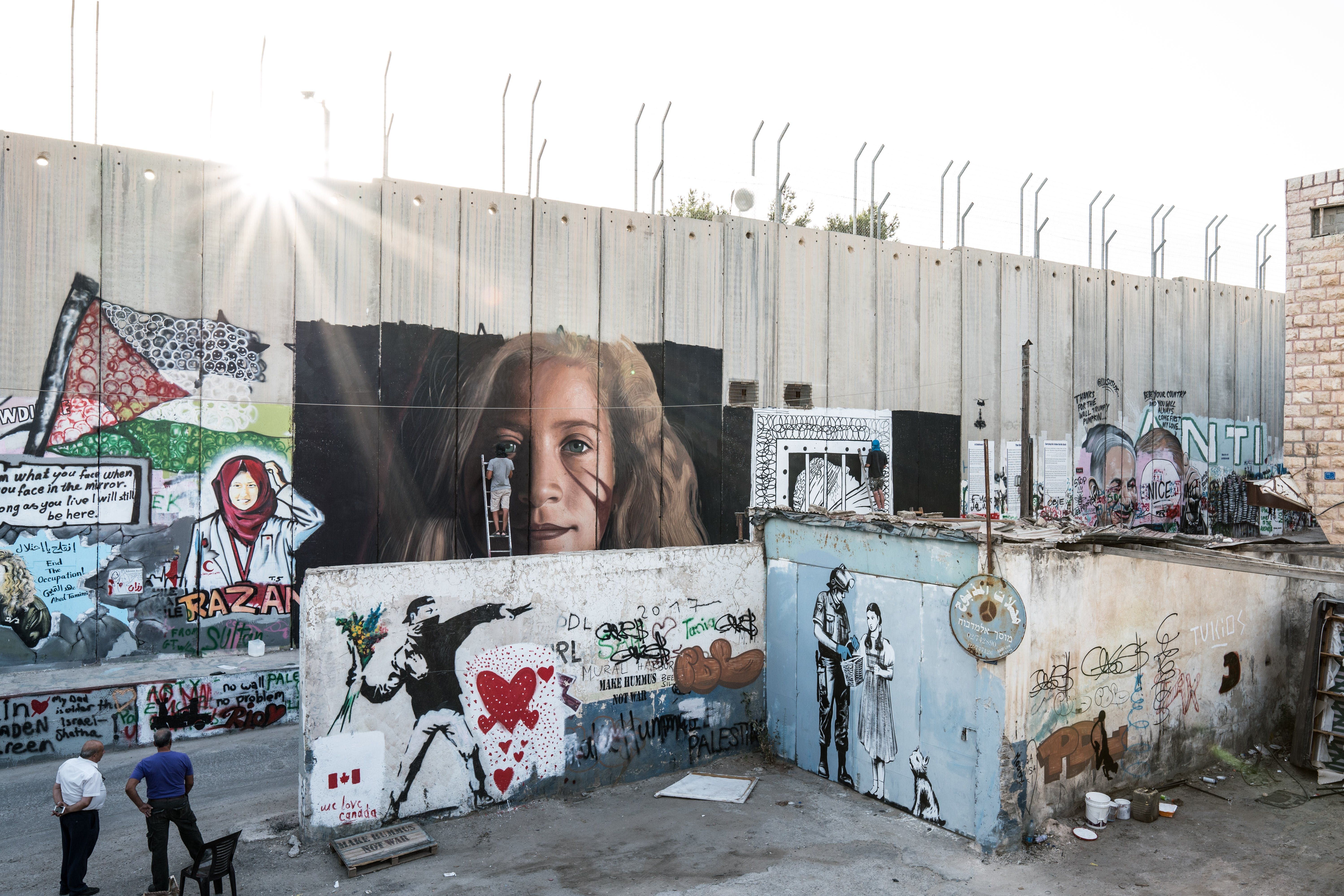 An Italian activist paints a portrait of Palestinian Ahed Tamimi on a part of the Israeli separation wall in Bethlehem on July 25, 2018.