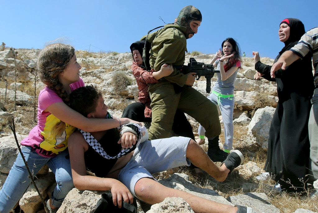 Palestinian women figth to free a Palestinian boy (bottom) held by an Israeli soldier (C) during clashes between Israeli security forces and Palestinian protesters following a march against Palestinian land confiscation to expand the nearby Jewish Hallamish settlement on August 28, 2015 in the West Bank village of Nabi Saleh near Ramallah.  AFP PHOTO / ABBAS MOMANI        (Photo credit should read ABBAS MOMANI/AFP/Getty Images)