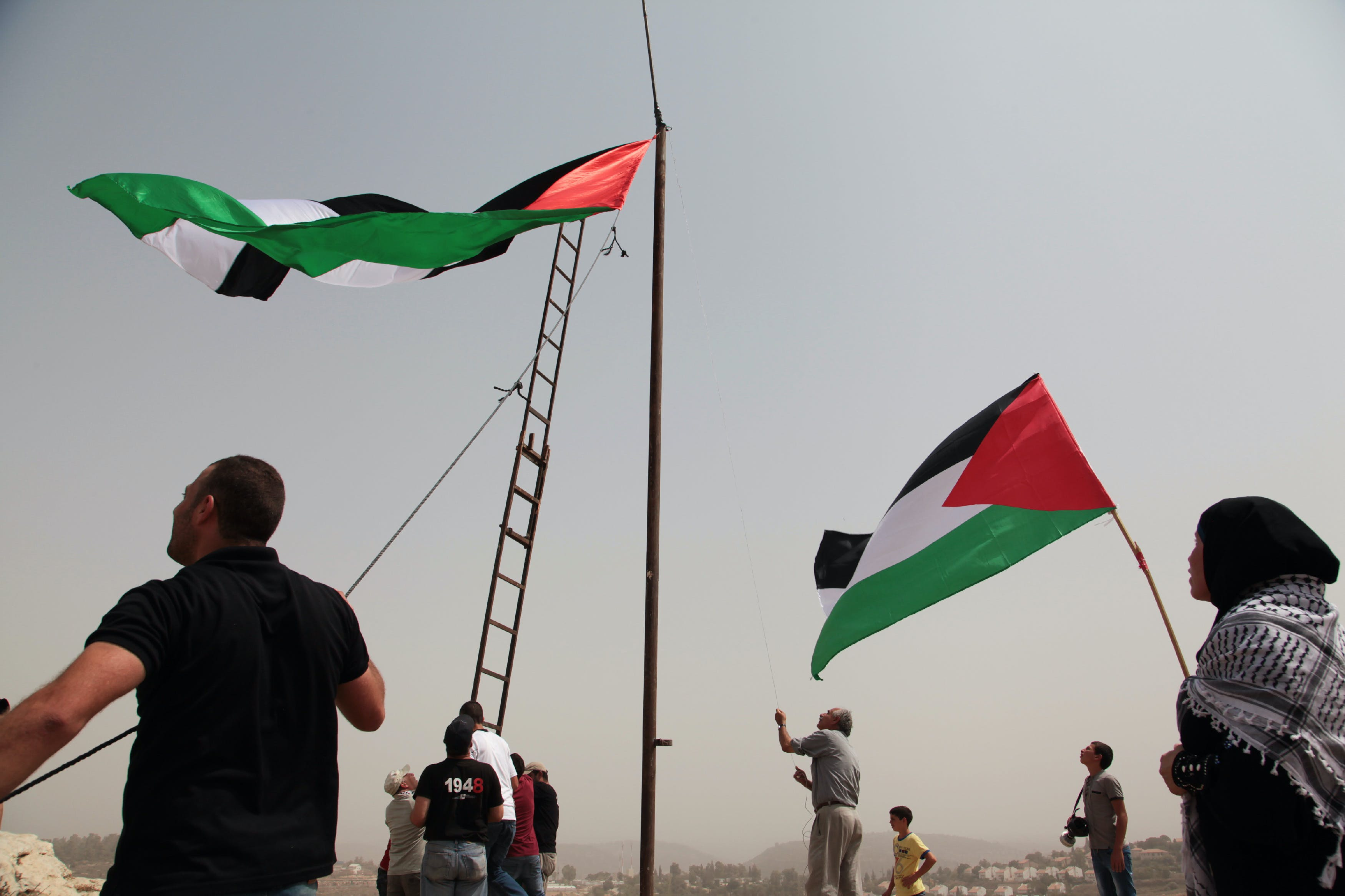 Palestinian protesters are raising a huge Palestine flag on flagpole in An Nabi Saleh on Sep 11, 2015. (Photo by Mohammad Alhaj/NurPhoto) (Photo by NurPhoto/NurPhoto via Getty Images)