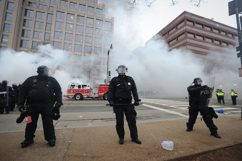 WASHINGTON, DC - JANUARY 20:  Police keep watch as firefighters put out a limousine fire after the vehicle was smashed by anti-Trump protesters on K Street on January 20, 2017 in Washington, DC. While protests were mostly peaceful, some turned violent. President-elect Donald Trump was sworn-in as the 45th U.S. President today.  (Photo by Mario Tama/Getty Images)