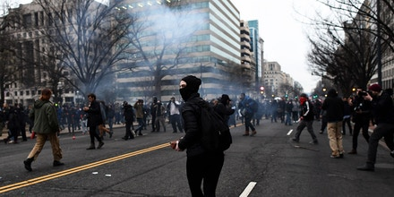 An anti-Trump protester throws bricks at police durig clashes in Washington, DC, on January 20, 2017. Masked, black-clad protesters carrying anarchist flags smashed windows and scuffled with riot police Friday in downtown Washington, blocks away from the route of the parade in honor of newly sworn-in President Donald Trump. Washington police arrested more than 90 people over acts of vandalism committed on the fringe of peaceful citywide demonstrations being held against Trump's inauguration. / AFP / Jewel SAMAD (Photo credit should read JEWEL SAMAD/AFP/Getty Images)