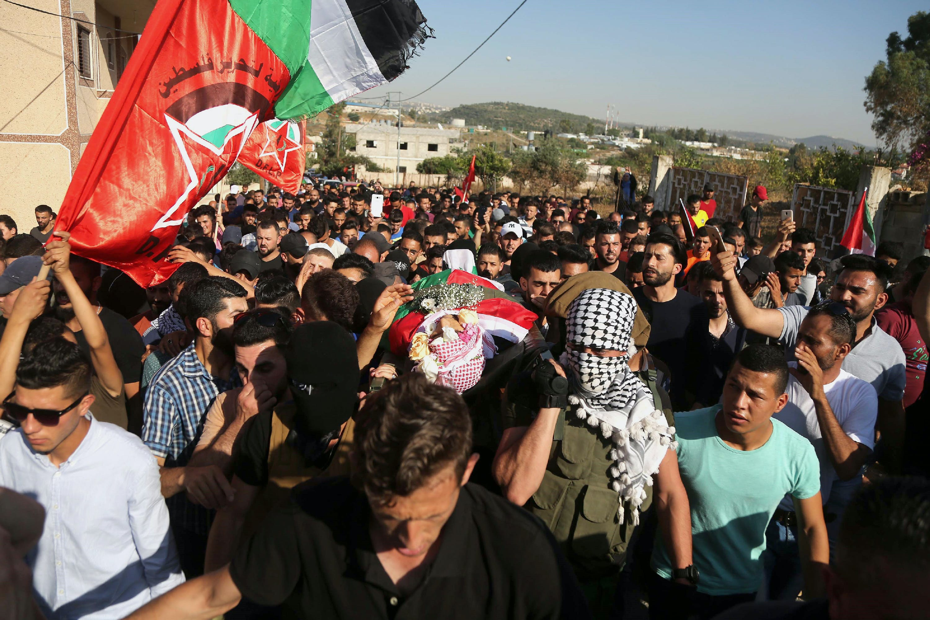 RAMALLAH, WEST BANK - JUNE 06: Palestinians carry the dead body of Ezz al-Tamimi, 21, who was killed by Israeli forces, at a checkpoint, as Israeli soldiers intervene them during his funeral ceremony near Nabi Saleh district of Ramallah, in West Bank on June 06, 2018. (Photo by Issam Rimawi/Anadolu Agency/Getty Images)