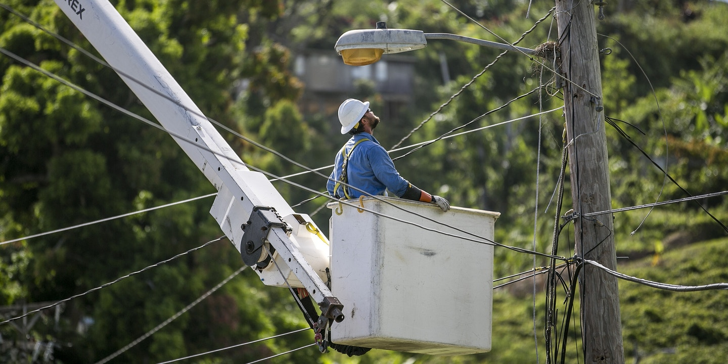 A Worker Stands In Cherry Picker While Fixing Power Lines On Utility Pole