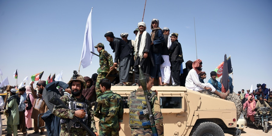 In this photo taken on June 17, 2018, Afghan Taliban militants and residents stand on a armoured Humvee vehicle of the Afghan National Army (ANA) as they celebrate a ceasefire on the third day of Eid in Maiwand district of Kandahar province. - Extraordinary scenes of Afghan Taliban and security forces spontaneously celebrating a historic ceasefire showed many fighters on both sides were fed up with the conflict, raising hopes that peace in the war-torn country was possible, analysts said. (Photo by JAVED TANVEER / AFP) / TO GO WITH Afghanistan-unrest-ceasefire,FOCUS by Allison Jackson        (Photo credit should read JAVED TANVEER/AFP/Getty Images)