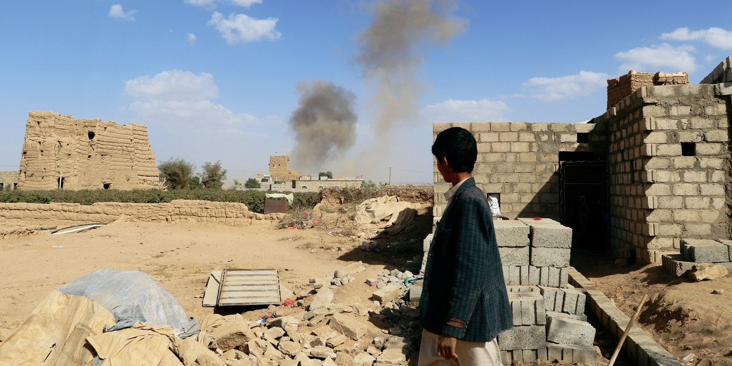 A boy looks at dust raising from the site of air strikes in Saada, Yemen February 27, 2018. REUTERS/Naif Rahma - RC17EDCF7290
