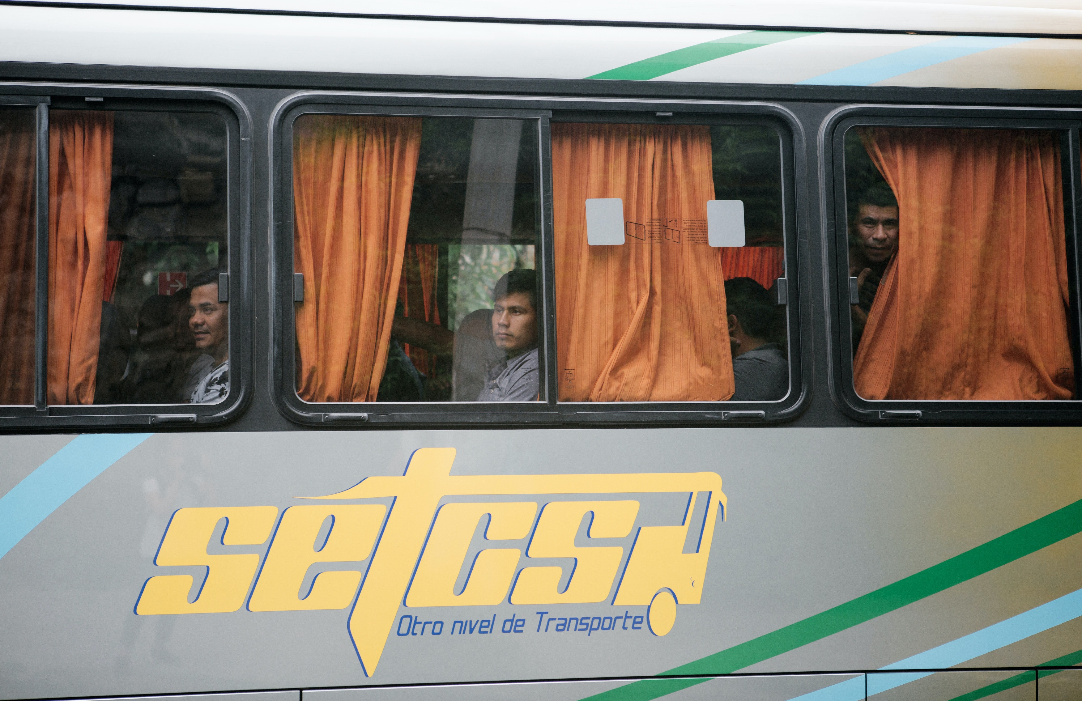 Deported migrants sit on a bus as they enter an immigration detention facility, called the Centro de Atención Integral para el Migrante (CAIM), in San Salvador, El Salvador.