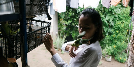 Iris Tobar plays with her pet parrot at her home in Jutiapa, El Salvador.