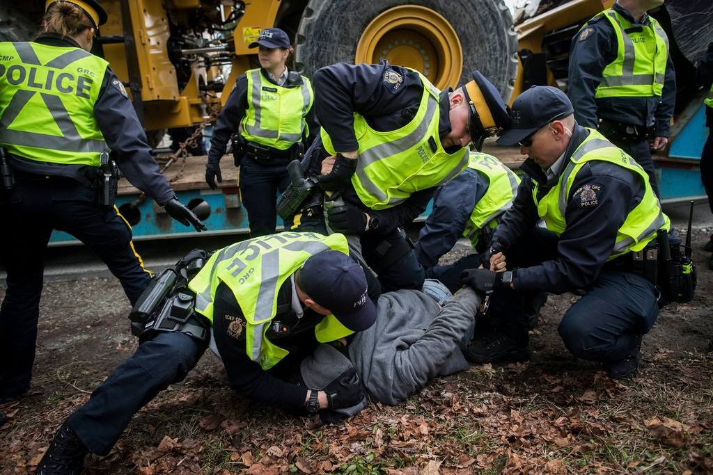 Dan Wallace, of the Kwakwaka'wakw First Nation on Quadra Island, is tackled and handcuffed by RCMP officers after attempting to talk to a young man that locked himself to a piece of heavy equipment being delivered to Kinder Morgan in Burnaby, B.C., on Monday March 19, 2018. Wallace was released a short time later without being charged. Numerous protesters who blockaded an entrance - defying a court order - were arrested earlier in the day while protesting the Kinder Morgan Trans Mountain pipeline expansion. (Darryl Dyck/The Canadian Press via AP)
