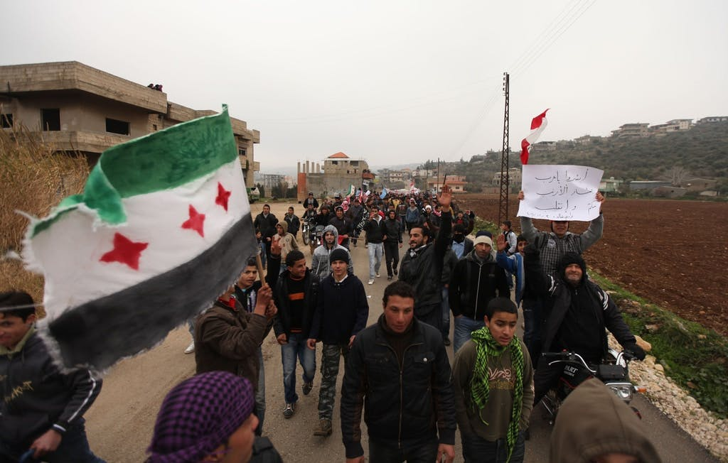 Manifestantes nas ruas de Wadi Khaled, na fronteira entre Líbano e Síria, durante um protesto contra o governo sírio, no dia 30 de dezembro de 2011, agitam uma antiga bandeira da Síria e um cartaz debochando do presidente Bashar al-Assad.