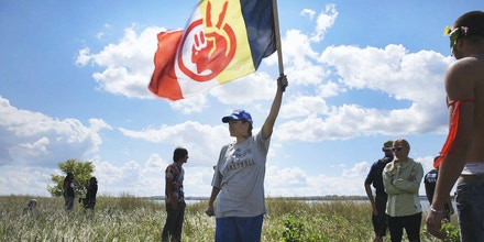 Red Fawn Fallis waves a flag symbolizing the American Indian Movement at Standing Rock on Aug. 20, 2016.