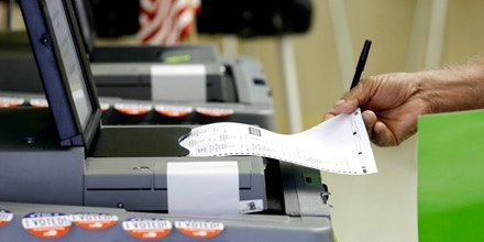 FILE - In this Aug. 30, 2016 file photo, a voter casts his primary vote in Hialeah, Fla. Hacking attempts of voting machines and leaked emails could alter the trajectory of the presidential campaign in its final weeks. These prospects worry people in both campaigns.  (AP Photo/Alan Diaz, File)