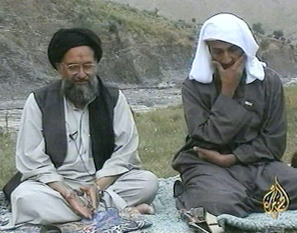 In this television image from Arab satellite station Al-Jazeera, Osama bin Laden, right, listens as his top deputy Ayman al-Zawahri speaks at an undisclosed location, in this image made from undated video tape broadcast by the station Monday April 15, 2002. Al-Jazeera editor-in-chief Ibrahim Hilal said the excerpts were from an hour-long video, complete with narration and graphics, delivered by hand to the station's Doha, Qatar offices a week ago. At bottom right is the station's logo. (AP Photo/Al-Jazeera/APTN)