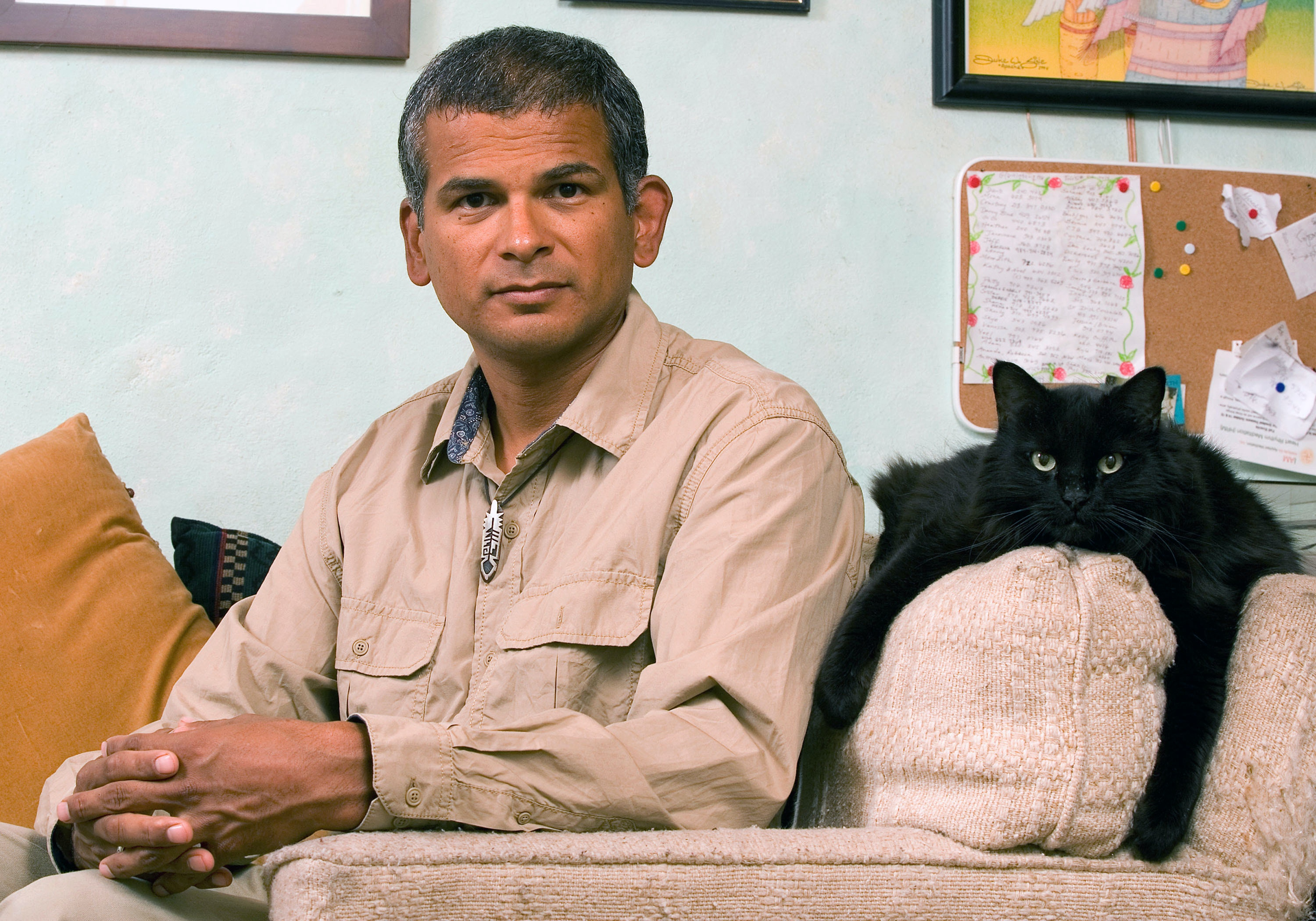 Rod Coronado poses with his cat, Nau, in his home in Tucson, Ariz. Thursday, Aug. 23, 2007. Coronado thinks of himself as an environmentalist, while others would prefer the term eco-terrorist. Renowned for helping sink whaling ships in the North Atlantic and firebombing a Michigan animal-research facility, he toured the country after prison time telling others how to make do-it-yourself Molotov cocktails.  (AP Photo/John Miller)