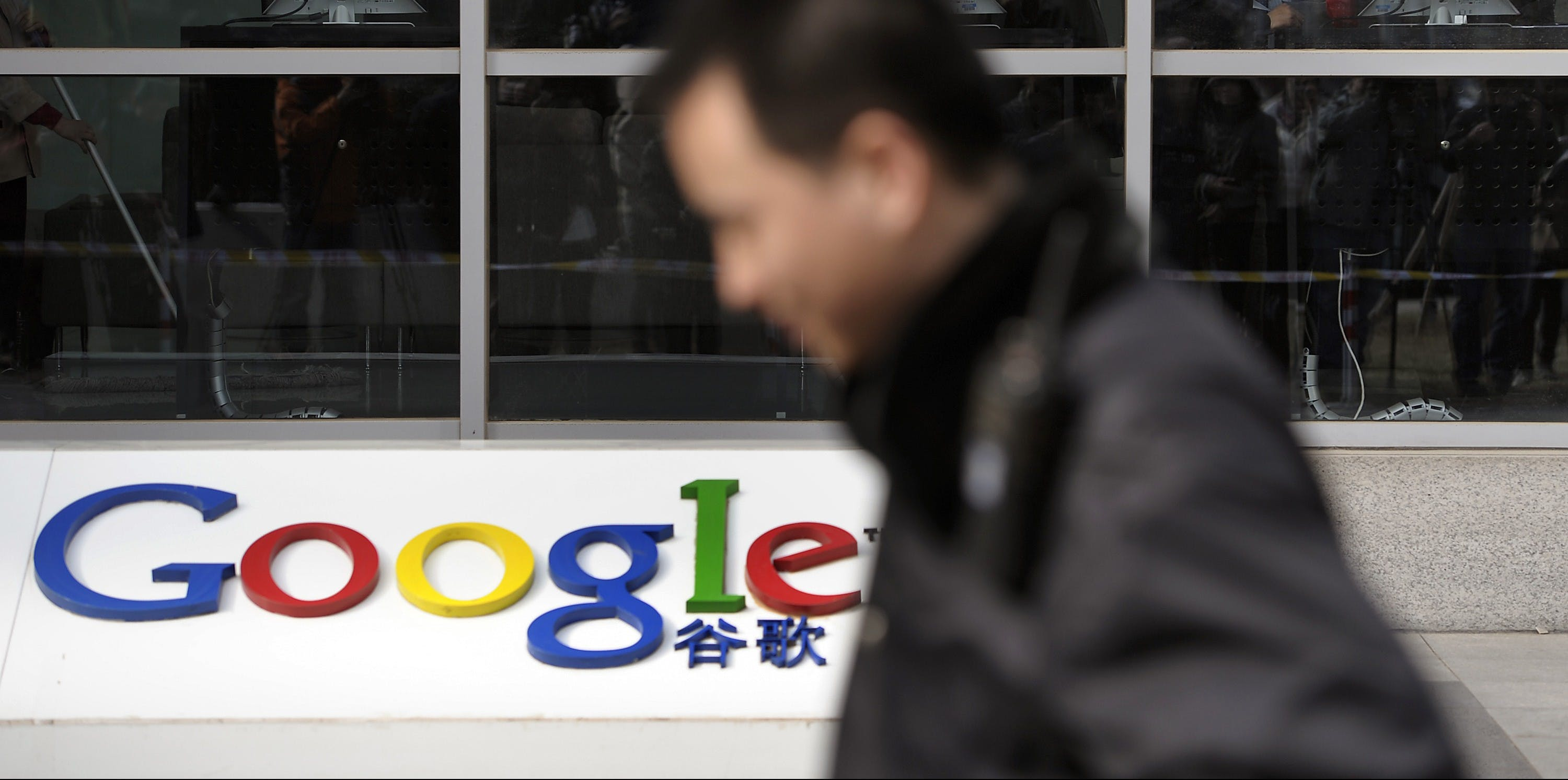 A security guard walks past while foreign visitors are seen inside the Google China headquarters in Beijing Tuesday, March 23, 2010. Google Inc. stopped censoring the Internet for China by shifting its search engine off the mainland Monday but said it will maintain other operations in the country. The maneuver attempts to balance Google's disdain for China's Internet rules with the company's desire to profit from an explosively growing market. (AP Photo/Andy Wong)